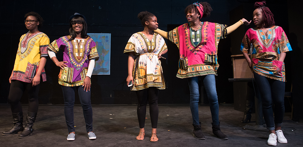 Five students are on stage showing off colorful, traditional African garb