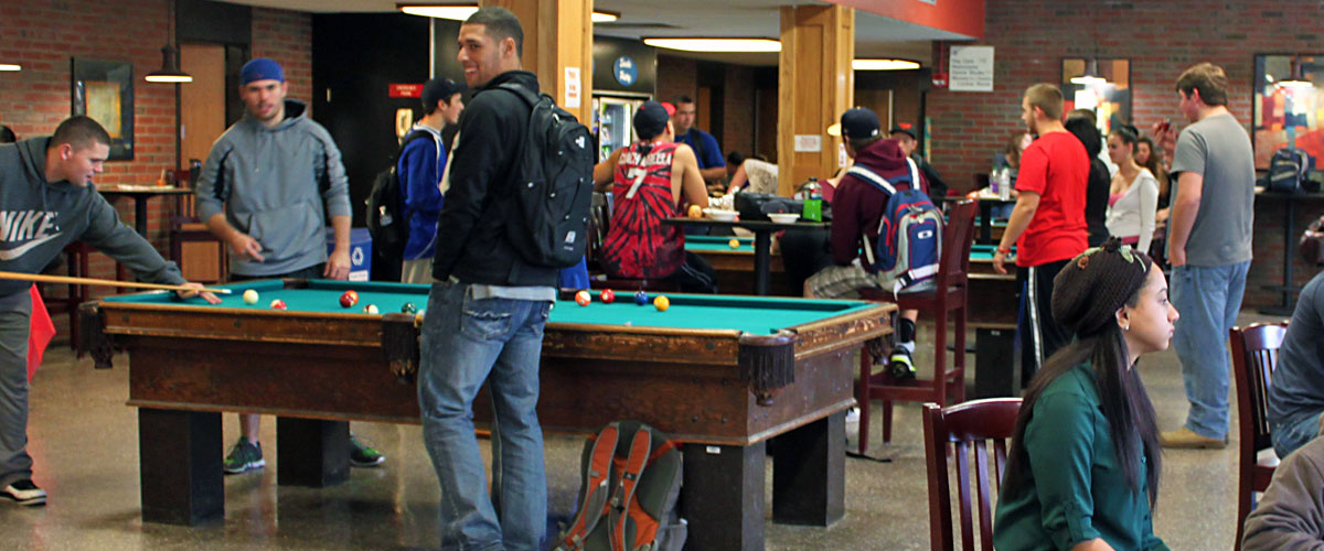 Students playing pool, standing, sitting anding talking, in the Sport and Fitness Center Lobby