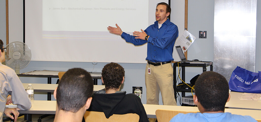 A professor actively engages a group of Electronic Equipment Technology Certificate students in a classroom.