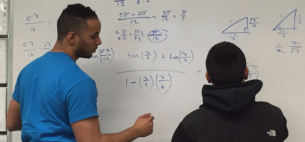Students at whiteboard completing math problems.