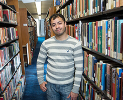 NECC alumnus and veteran stands in the library