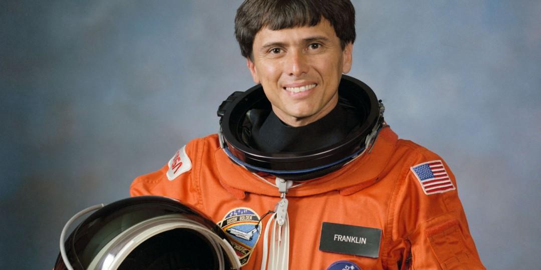 Astronaut Chang-Diaz in his NASA space suit, holding helmet.
